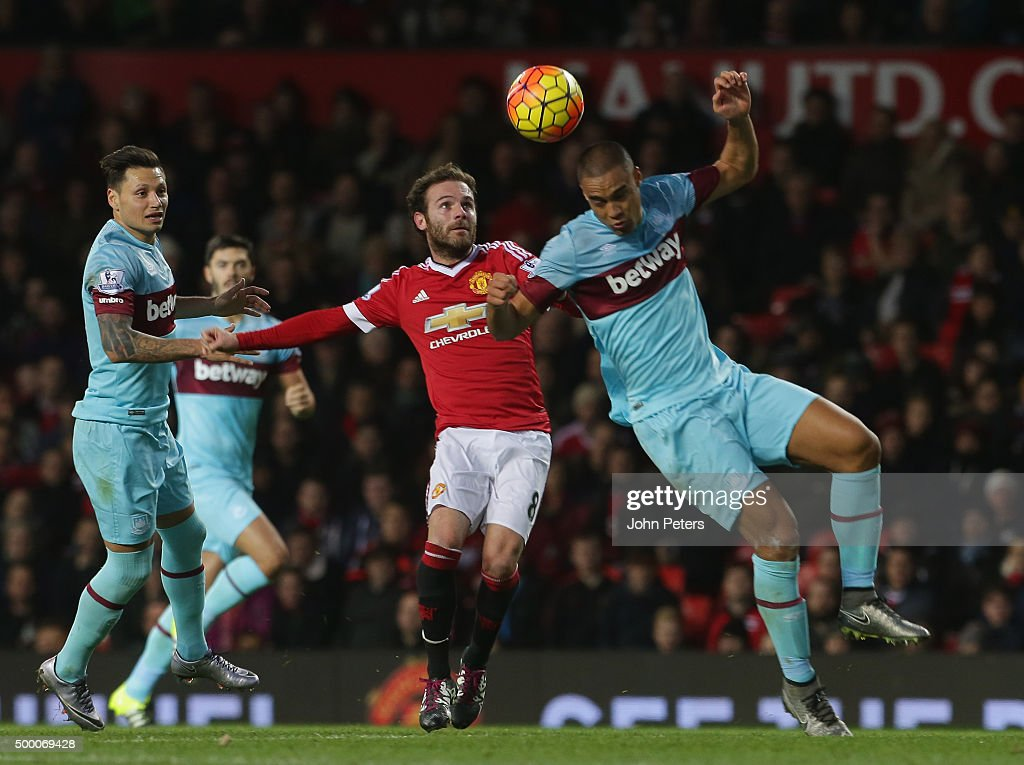 Juan Mata of Manchester United in action with Winston Reid of West Ham United during the Barclays Premier League match between Manchester United and West Ham United at Old Trafford on December 05, 2015 in Manchester, England.