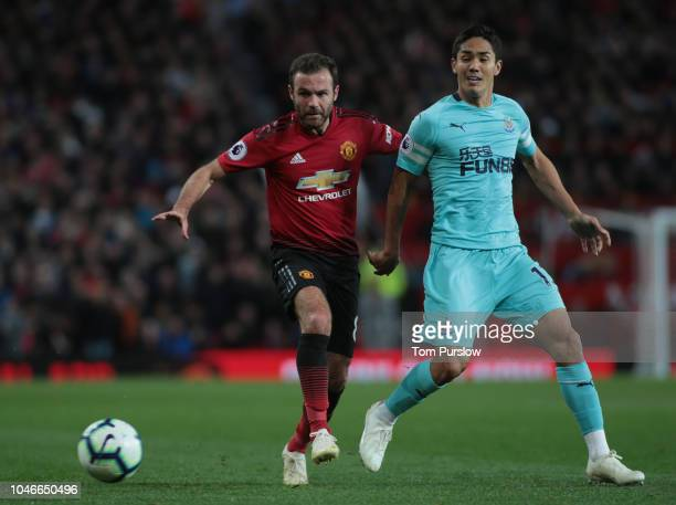 Juan Mata of Manchester United in action with Yoshinori Muto of Newcastle United during the Premier League match between Manchester United and...