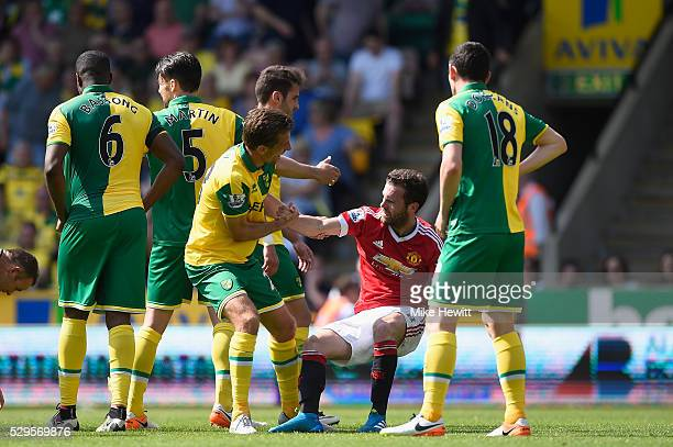 Juan Mata of Manchester United is helped up by Gary O'Neil of Norwich City during the Barclays Premier League match between Norwich City and...