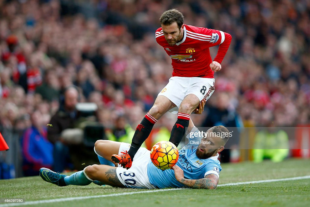 Juan Mata of Manchester United is tackled by Nicolas Otamendi of Manchester City during the Barclays Premier League match between Manchester United and Manchester City at Old Trafford on October 25, 2015 in Manchester, England.
