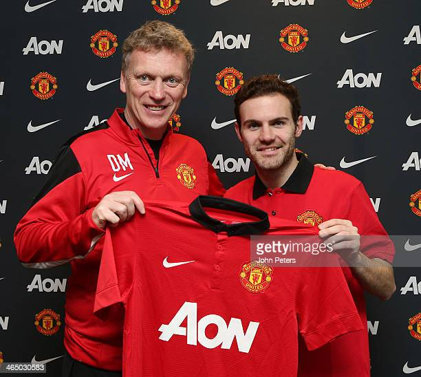 Juan Mata of Manchester United poses with Manchester United Manager David Moyes and a Manchester United shirt after signing his contract with the...