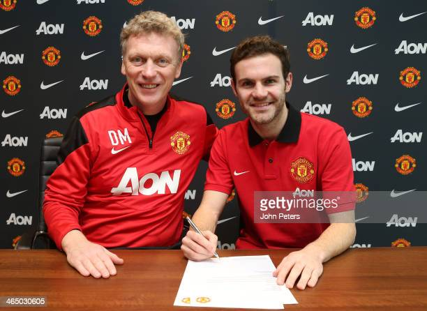 Juan Mata of Manchester United poses with Manchester United Manager David Moyes after signing his contract with the club at Aon Training Complex on...