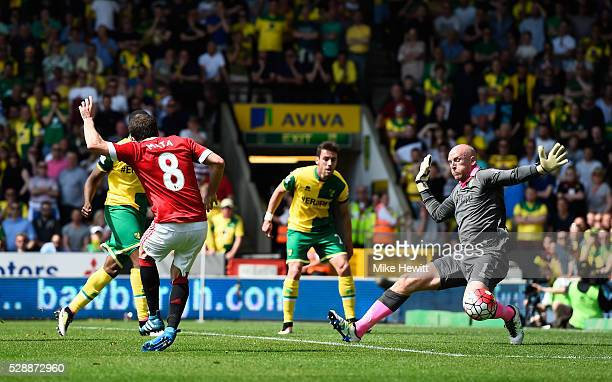 Juan Mata of Manchester United scores his team's first goal past John Ruddy of Norwich City during the Barclays Premier League match between Norwich...