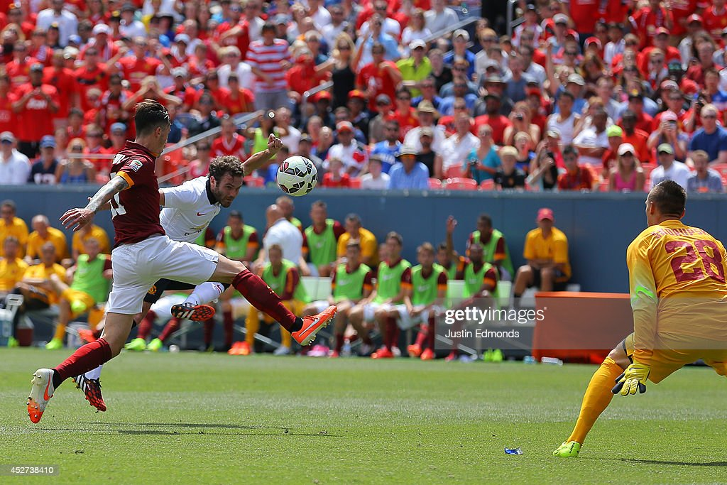 Juan Mata #8 of Manchester United scores past Alessio Romangnoli #11 and goalkeeper Lukasz Skorupski #28 of AS Roma during the first half of an International Champions Cup match at Sports Authority Field at Mile High on July 26, 2014 in Denver, Colorado.