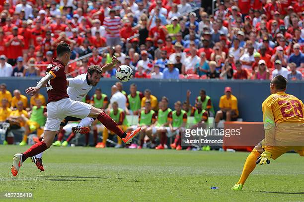 Juan Mata of Manchester United scores past Alessio Romangnoli and goalkeeper Lukasz Skorupski of AS Roma during the first half of an International...