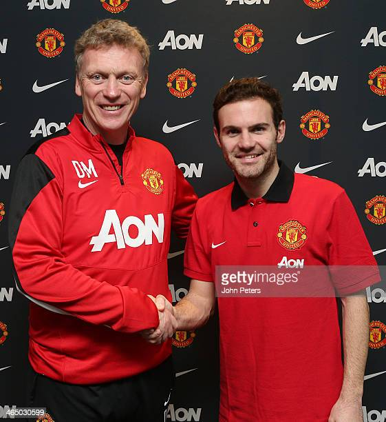 Juan Mata of Manchester United shakes hands with Manchester United Manager David Moyes after signing his contract with the club at Aon Training...