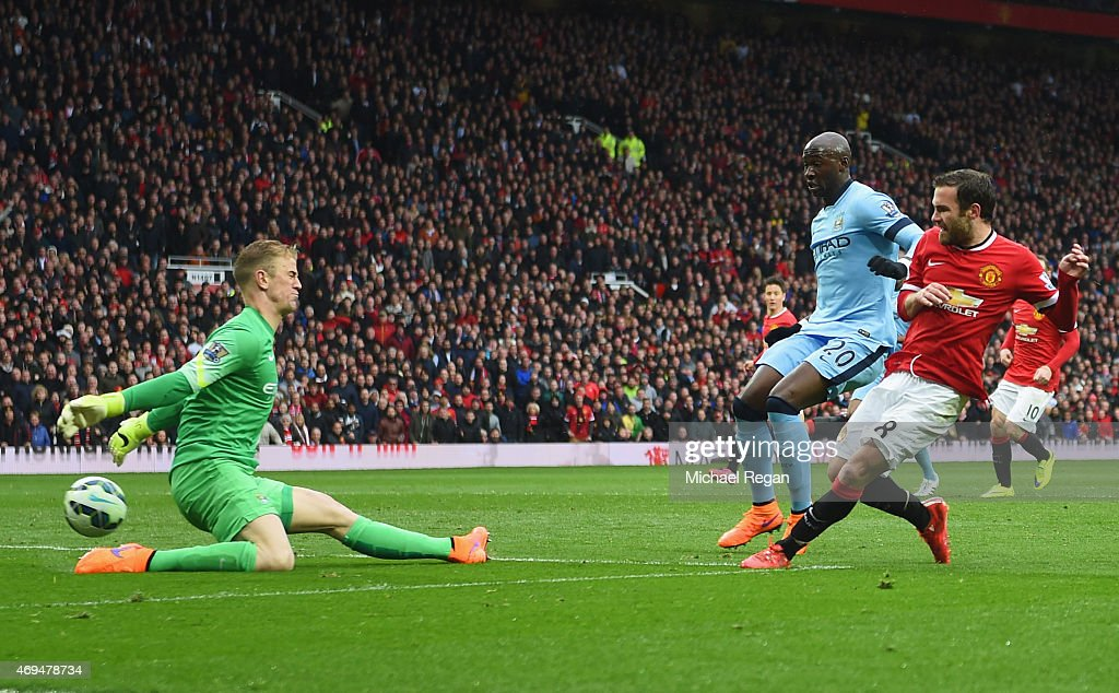 Juan Mata of Manchester United shoots past Joe Hart of Manchester City to score their third goal during the Barclays Premier League match between Manchester United and Manchester City at Old Trafford on April 12, 2015 in Manchester, England.
