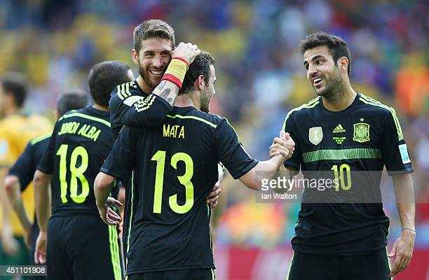 Juan Mata of Spain celebrates scoring his team's third goal with teammates Sergio Ramos and Cesc Fabregas during the 2014 FIFA World Cup Brazil Group...