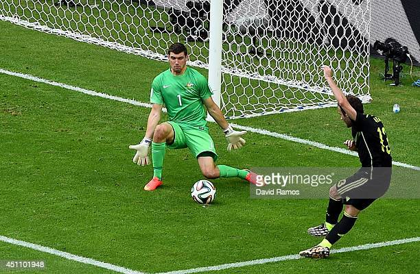 Juan Mata of Spain scores his team's third goal past Mathew Ryan of Australia during the 2014 FIFA World Cup Brazil Group B match between Australia...