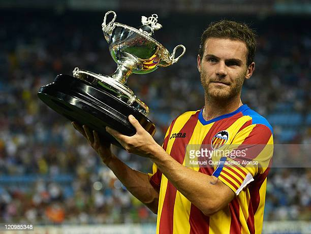 Juan Mata of Valencia lifts the winners trophy after the Orange Trophy match between Valencia and Roma at Estadio Mestalla on August 12 2011 in...