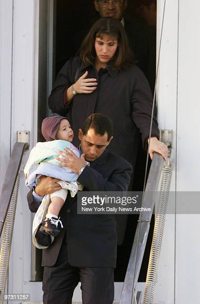 Juan Miguel Gonzalez caries his 6monthold son Hianny as he leaves plane at Dulles International Airport followed by his wife Nercy Carmenate Castillo...