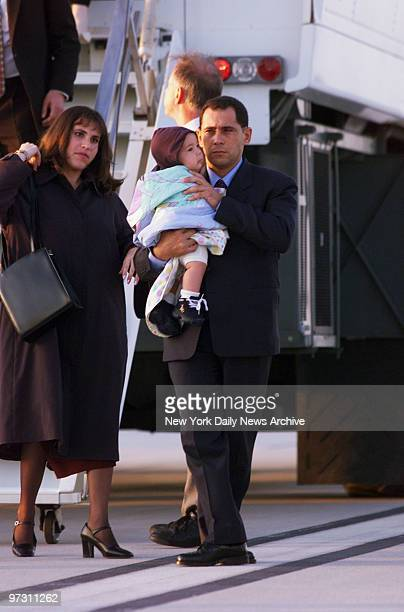 Juan Miguel Gonzalez caries his 6monthold son Hianny as he leaves plane at Dulles International Airport with his wife Nercy Carmenate Castillo...