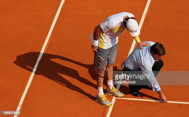 Juan Monaco of Argentina checks a ball mark near to the line with the umpire against Novak Djokovic of Serbia in their third round match during day...