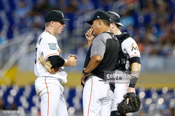 Juan Nieves of the Miami Marlins talks with Jeff Brigham and Chad Wallach on the mound in the first inning against the Toronto Blue Jays at Marlins...