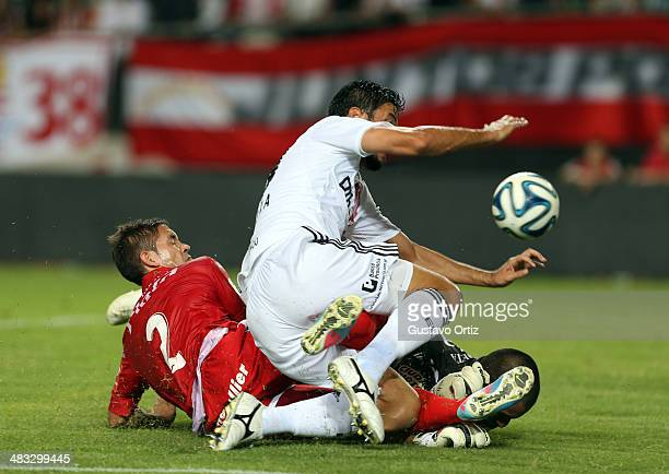 Juan Olivera of Estudiantes srtuggles for the ball with Miguel Torren and Nereo Fernandez, of Argentinos Juniors, and scores during a match between...