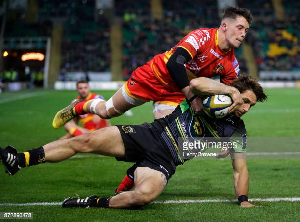 Juan Pablo Estelles of Northampton Saints scores their first try despite the efforts of Joe Goodchild of Dragons during the AngloWelsh Cup match...