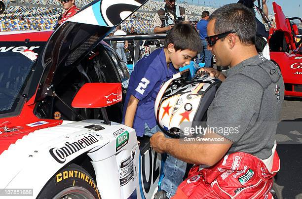 Juan Pablo Montoya driver of the Chip Ganassi Racing with Felix Sabates BMW Riley and son Sebastian look over the car prior to the start of the Rolex...