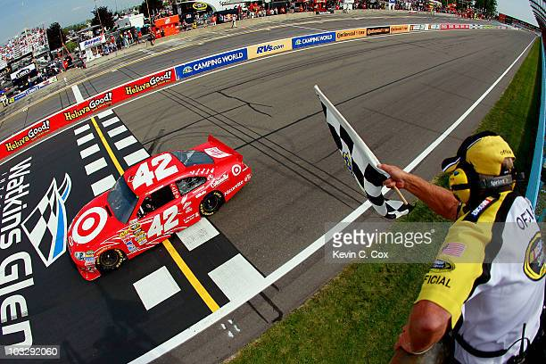 Juan Pablo Montoya driver of the Target Chevrolet crosses the finish line to win the NASCAR Sprint Cup Series Heluva Good Sour Cream Dips at Watkins...