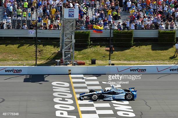 Juan Pablo Montoya of Colombia driver of the PPG Team Penske Chevrolet crosses the finish line to win the Pocono INDYCAR 500 at Pocono Raceway on...