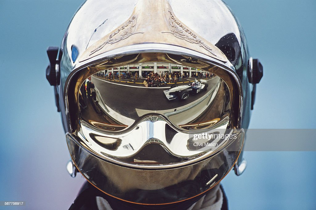Juan Pablo Montoya of Colombia driving the BMW WilliamsF1 Team Williams-BMW FW25 is reflected in the visor of a firemanduring practice for the Rhone-Poulenc French Grand Prix on 5 July 2003 at the Circuit de Nevers Magny-Cours in Magny Cours, France.