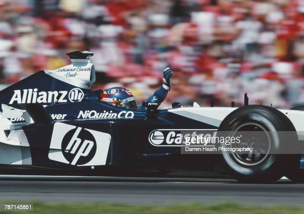 Juan Pablo Montoya of Colombia salutes the crowd after driving the BMW Williams F1 Team Williams FW25 BMW V10 to victory in the Formula One German...