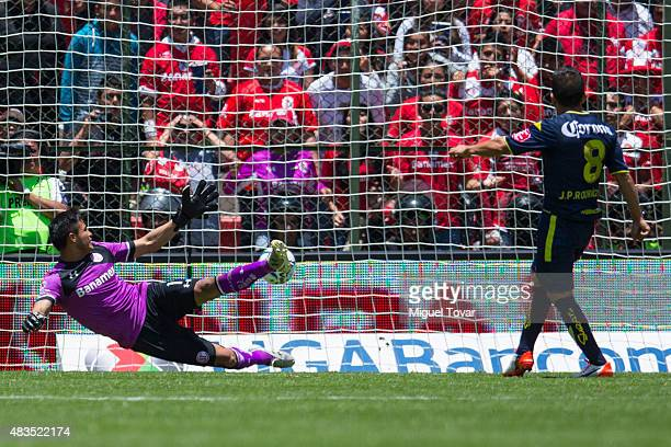 Juan Pablo Rodriguez of Morelia scores the first goal of his team from the penalty spot past Alfredo Talavera goalkeeper of Toluca during a 3rd round...