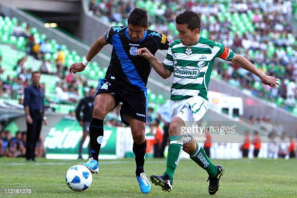 Juan Pablo Rodriguez of Santos struggles for the ball with Raul Rico of Puebla during a match as part of the Clausura 2011 at Corona Stadium on April...
