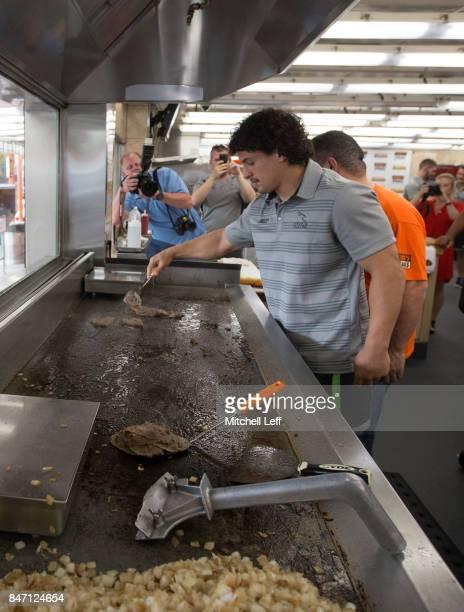 Juan Pablo Socino of the Newcastle Falcons makes a cheesesteak at Geno's Steaks on September 14 2017 in Philadelphia Pennsylvania