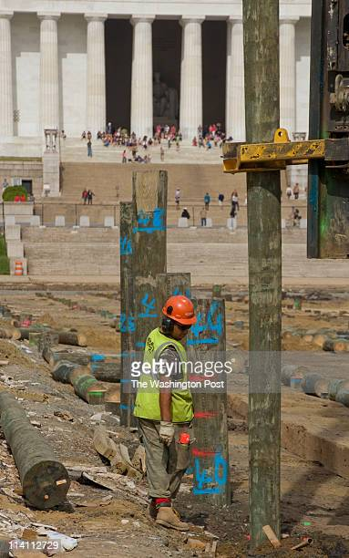 Juan Perez helps operator Matt Deshong guide a pole into place as the Lincoln Memorial Reflecting Pool Project continues in Washington DC on Monday...
