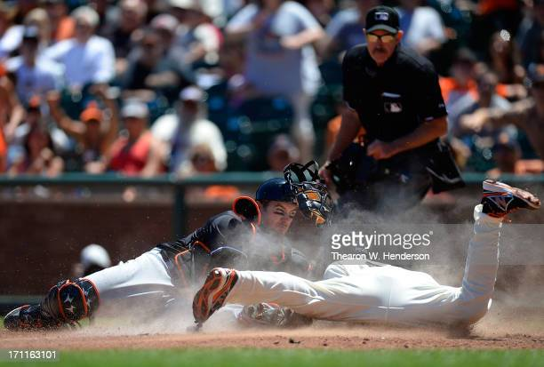 Juan Perez of the San Francisco Giants attempting to score on a squeeze play is tagged out by Jeff Mathis of the Miami Marlins in the fifth inning at...