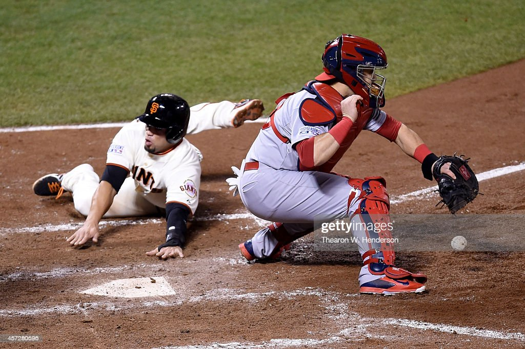 Juan Perez #2 of the San Francisco Giants slides home safely as catcher Tony Cruz #48 of the St. Louis Cardinals is unable to catch the ball in the sixth inning during Game Four of the National League Championship Series at AT&T Park on October 15, 2014 in San Francisco, California.