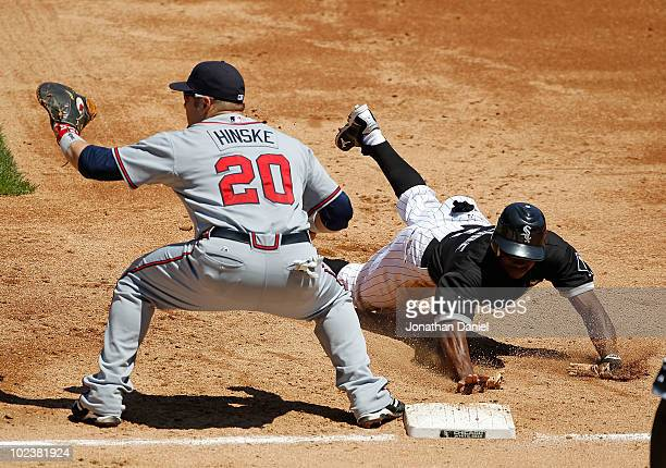 Juan Pierre of the Chicago White Sox dives back to first base as Eric Hinske of the Atlanta Braves awaits the throw at US Cellular Field on June 24...