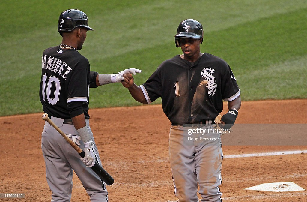 Juan Pierre #1 of the Chicago White Sox is welcomed home by Alexei Ramirez #10 of the Chicago White Sox after scoring in the fourth inning to give the White Sox a 1-0 lead over the Colorado Rockies during Interleague play at Coors Field on June 29, 2011 in Denver, Colorado.