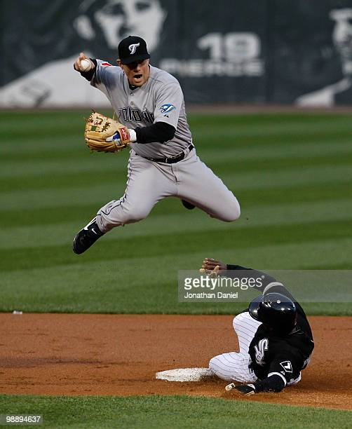 Juan Pierre of the Chicago White Sox slides into second base and forces Aaron Hill of the Toronto Blue Jays to leap and miss the doubleplay relay...
