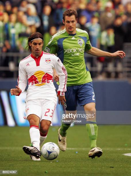 Juan Pietravallo of the New York Red Bulls kicks the ball as Nate Jaqua of the Seattle Sounders FC pursues in the first half of their opening match...