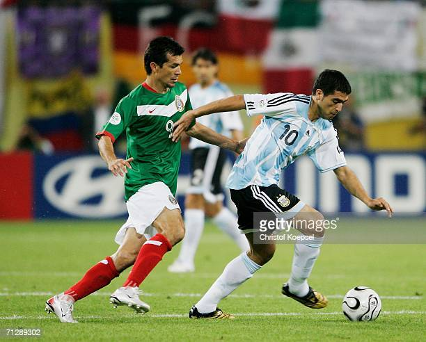Juan Riquelme of Argentina steers the ball away from Jared Borgetti of Mexico during the FIFA World Cup Germany 2006 Round of 16 match between...