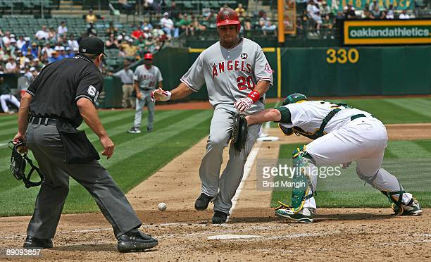 Juan Rivera of the Los Angeles Angels of Anaheim is safe at home as Oakland Athletics catcher Landon Powell can't handle the throw during the game at...