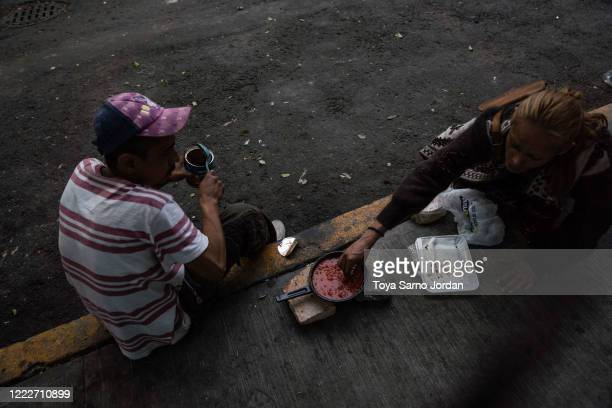 Juan Rodríguez Molina and his partner Nicky Castelan prepare a meal on a sidewalk in the Buenavista neighborhood on June 21 2020 in Mexico City...