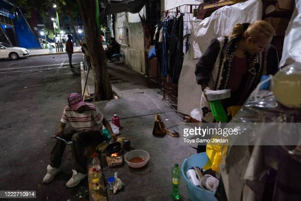 Juan Rodríguez Molina and his partner Nicky Castelan prepare dinner on a sidewalk in the Buenavista neighborhood on June 21 2020 in Mexico City...