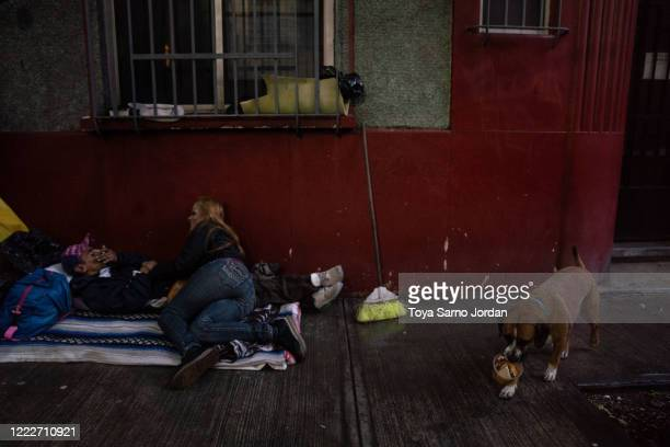 Juan Rodríguez Molina and his partner Nicky Castelan talk as they lie on a makeshift bed on the sidewalk in the Buenavista neighborhood on June 20...