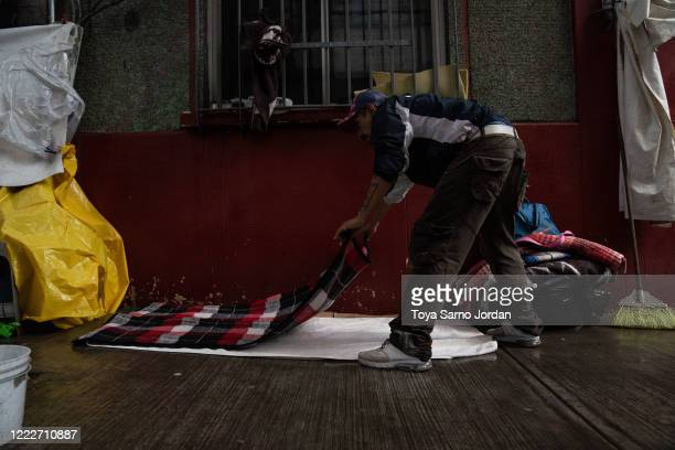 Juan Rodríguez Molina prepares a makeshift bed on a sidewalk in the Buenavista neighborhood on June 20 2020 in Mexico City Mexico Nicky Castelan a...