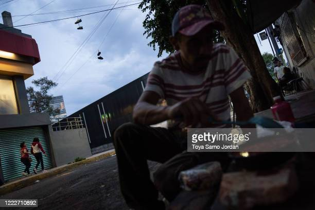 Juan Rodríguez Molina prepares dinner on a sidewalk in the Buenavista neighborhood on June 21 2020 in Mexico City Mexico Nicky Castelan a HIV...
