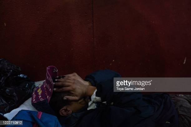 Juan Rodríguez Molina rubs his eyes as he lies on a makeshift bed on a sidewalk in the Buenavista neighborhood on June 20 2020 in Mexico City Mexico...