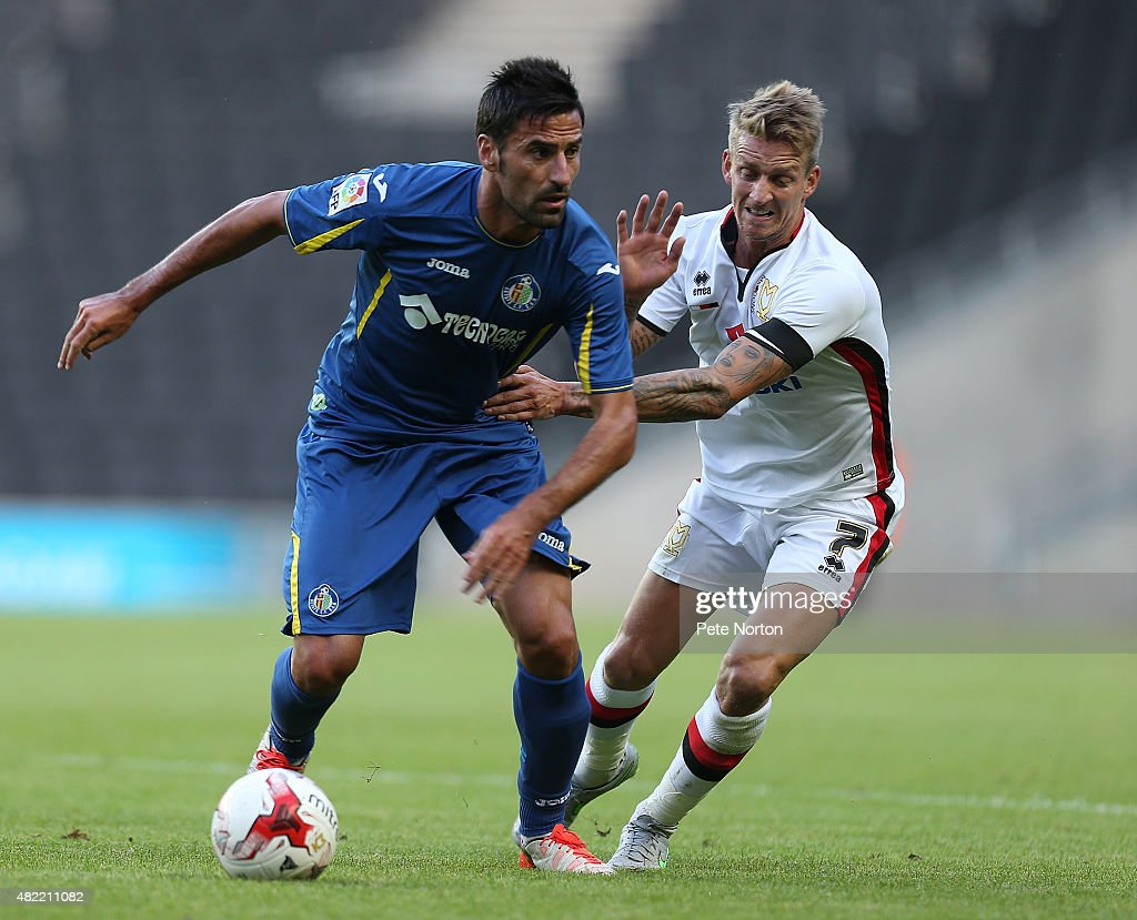 Juan Rodriguez of Getafe CF looks to move away with the ball from Carl Baker of MK Dons during the Pre-Season Friendly match between K Dons and Getafe CF at Stadium mk on July 28, 2015 in Milton Keynes, England.