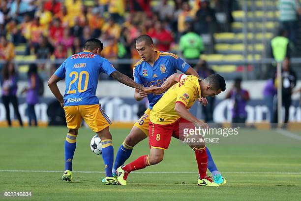 Juan Rodriguez of Morelia vies for the ball with Javier Aquino and Guido Pizarro of Tigres during their Mexican Apertura 2016 tournament football...