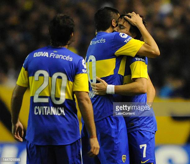 Juan Roman Riquelme hugs Pablo Mouche author of the goal while Dario Cvitanich walks to join them during a match as part of the Santander...