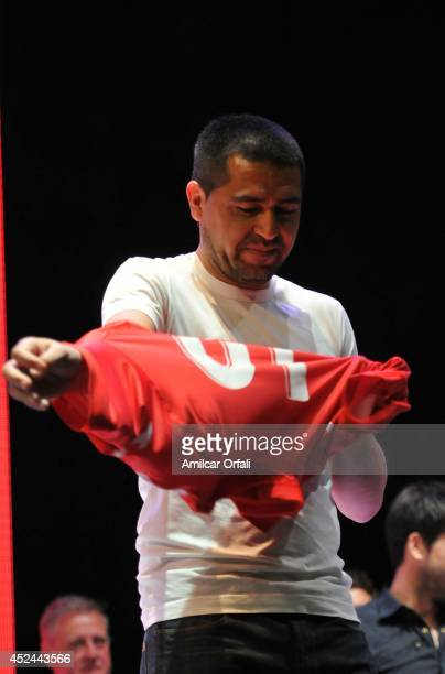 Juan Roman Riquelme tries on his jersey during a press conference after his official unveiling as a new Argentinos Jrs player at Panamericano Hotel...