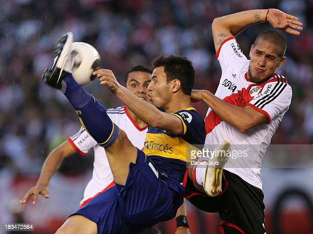 Juan Sanchez Miño of Boca Juniors struggles for the ball with Jonatan Maidana of River Plate during a match between River Plate and Boca Juniors as...