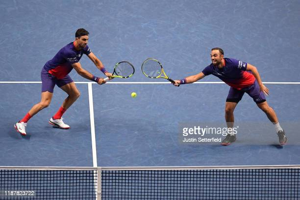 Juan Sebastian Cabal and Robert Farah of Colombia stretch to play a shot in their doubles match against Kevin Krawietz of Germany and Andreas Mies of...