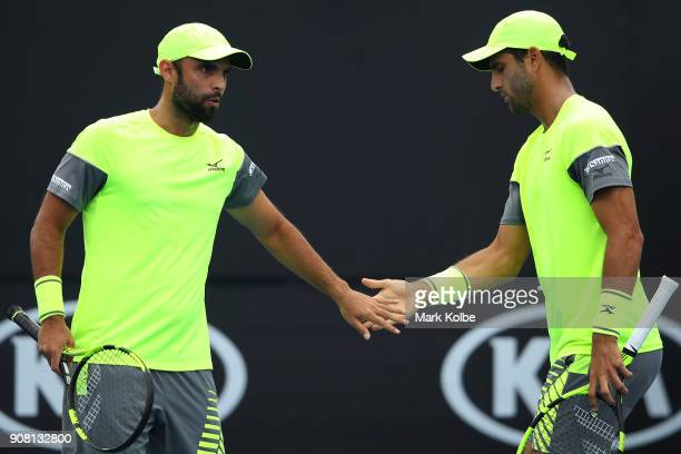Juan Sebastian Cabal of Colombia and Robert Farah of Colombia talk tactics in their third round men's doubles match against Leander Paes of India and...
